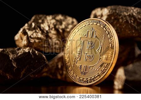 Shiny Golden Bitcoin Being Biggest Cryptocurrency Worldwide Together With Lumps Of Gold On Black Bac