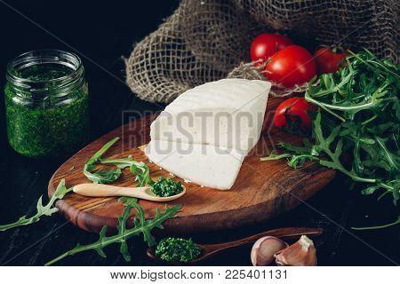 Traditional Caucasian Homemade Cheese On Wooden Board, With Pesto, Rukolla And Fresh Organic Tomatoe