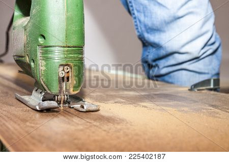 Diy Worker With Safety Glasses Cutting Wooden Panel With Jig Saw