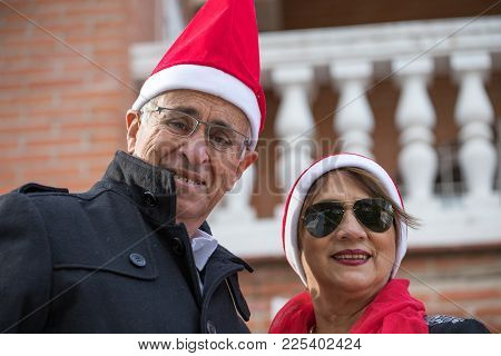 Senior Married Couple Pose With A Pope Noel Cap In The Garden Of Their Home