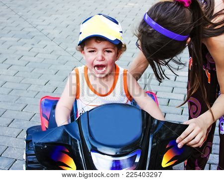 A Little Boy Is Capricious And Crying, Sitting On A Children's Atv Near The House. Children's Games