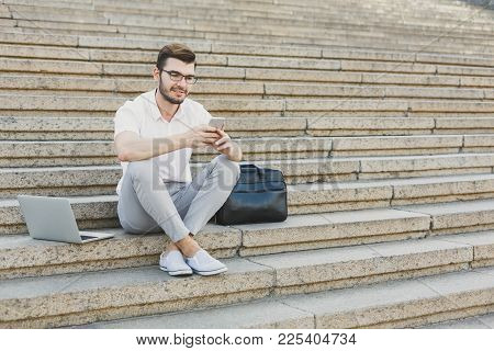 Serious Businessman Messaging On Smartphone Outdoors. Young Pensive Salesman Working With Mobile And