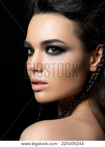 Beauty Portrait Of Young Woman. Perfect Skin And Evening Makeup. Model Posing Over Black Background.