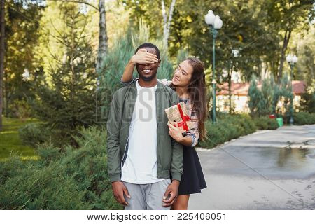 Young Asian Woman With Giftbox Closing Her Boyfriend Eyes To Make Surprise For Him, Walking In Park