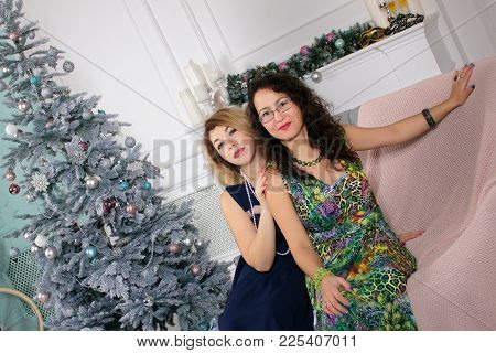 Christmas Holiday Happy Middle-aged Women Friends Sitting On A Sofa And Hugging In Christmas Decorat