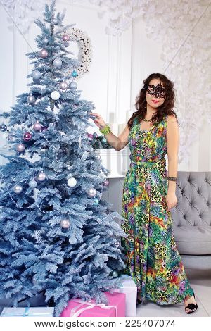 Beutiful Asian Woman In A Black Festive Mask Standing Near Christmas Tree In A Colorful Long Dress.