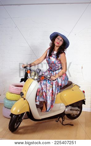 Studio Portrait Of A Happy Young Asian Woman On Scooter
