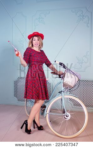 Beautiful Middle-aged Woman Cowgirl With Shotgun In Her Hand Standing Near Bicycle In Red Dress And