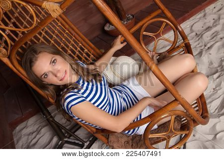 Outdoors Lifestyle Fashion Portrait Of Blong Young Woman Sitting On Swing On The Beach. Wooden House