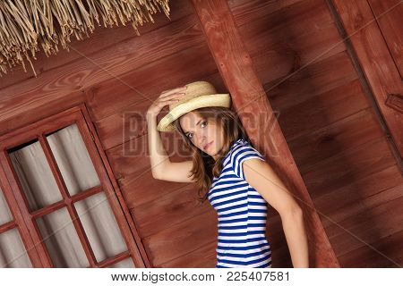 Beautiful Woman In A Striped Shirt And A Hat Standing On The Veranda Of A Summer Country House