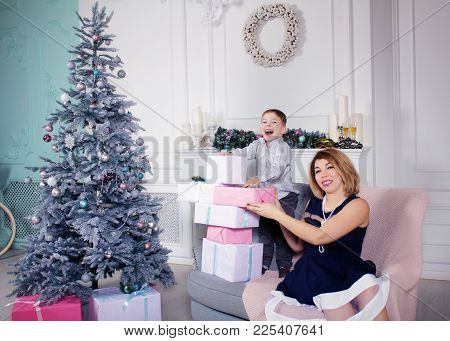 Happy Family - Pretty Mother And Her Little Son With Christmas Tree And Presents At Living Room.
