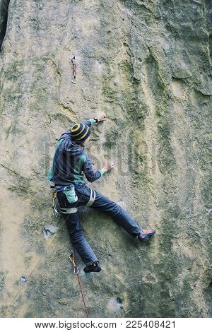 A Man Climbs The Rock On A Climbing Route.