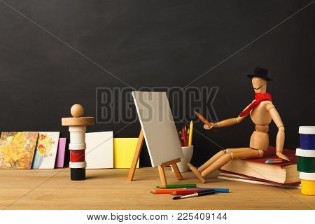 Art Background. Wooden Marionette Artist In Hat Sitting On Old Book And Painting Against Empty Class