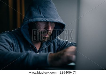 Male Hacker In A Sweatshirt With A Hood Sits Behind A Laptop