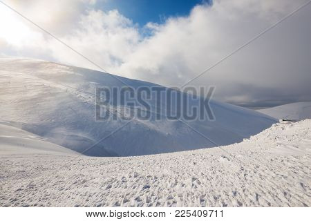 Severe Winter Landscape - A Mountain Range Covered With Snow, Lit By The Sun, During A Blizzard. Whi