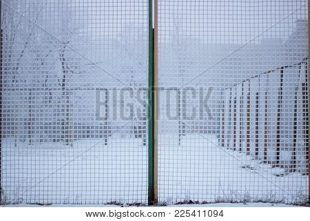 Snowed Sport Yard Behind Frosty Metal Grid In Winter