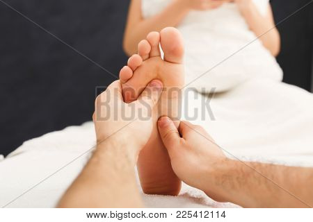 Leg Massage. Physiotherapist Pressing Specific Spots On Female Foot. Professional Health And Wellnes