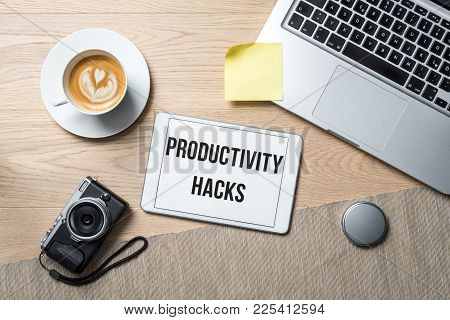 Productivity Hacks Writing On Tablet With Camera, Coffee Mug And Laptop Lying On Photography Office