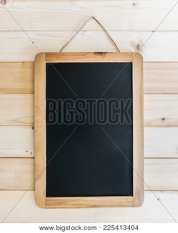 Blank Black Chalkboard Frame With Copyspace Hanging On Pine Wood Wall For Announcement And Restauran