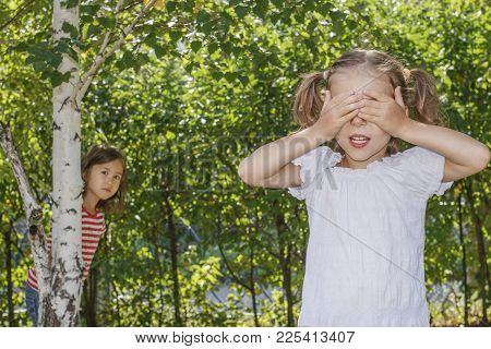 Two Sisters Playing Hide And Seek In The Park