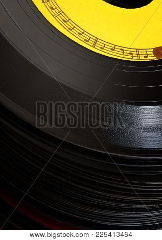A Border Of Notes And Staff On The Top Record Of A Stack Of Old 45 Rpm Records.