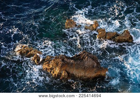 The Rocks Look Out From The Raging Blue Sea. Blue Waves And White Foam Around Rocks And Rocks. View