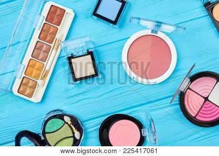 Multicolored Eyeshadows Set, Top View. Compact Eyeshadows And Blushers Collection, Blue Wooden Backg