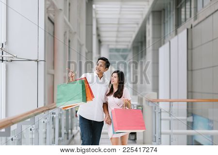 Happy Asian Couple Holding Colorful Shopping Bags And Enjoying Shopping, Having Fun Together In Mall