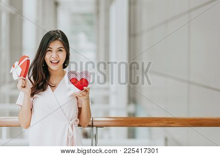 Beautiful Happy Smiling And Cheeful Asian Woman Holding Gift Box With Red Heart Inside On Valentine