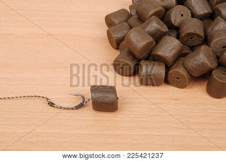 Fishing Bait With Hook And Brown Pre-drilled Halibut Pellets For Carp Fishing Isolated On Wood Backg
