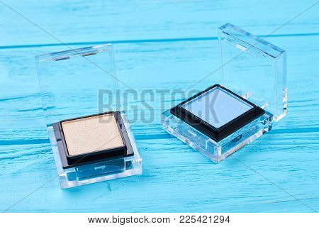 Colorful Eyeshadows On Wooden Background. Blue And Beige Eyeshadows On Blue Background. Fashion Make