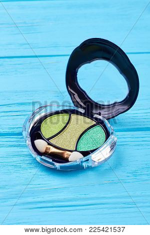 Green Color Eyeshadow, Wooden Background. Palette Of Shiny Eyeshadows In Compact Box On Color Backgr