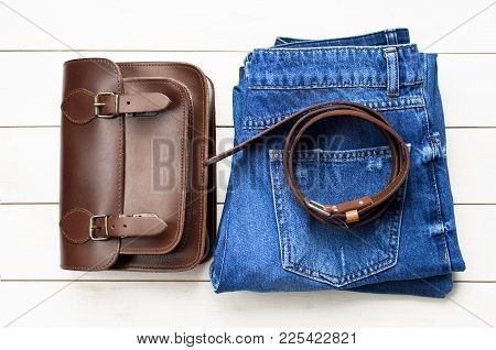Top View Jeans, Brown Leather Bag And A Leather Belt On A Light Wooden Background. Details Of Beauti