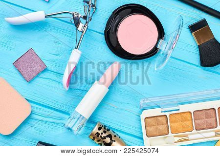 Woman Stylish Makeup Accessories. Eyelashes Curler, Eyeshadows, Lipstick, Face Powder On Blue Wooden