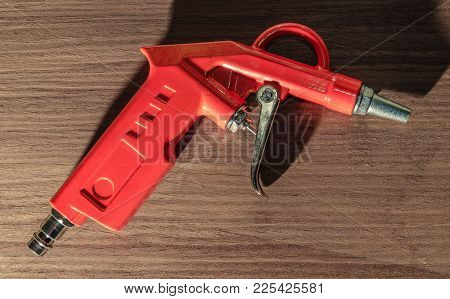 Orange Air Gun Close-up On Wooden Background