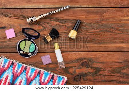 Wooden Background With Cosmetics. Pink Toiletry Bag And Different Cosmetics Products On Brown Backgr