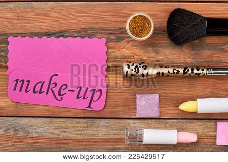 Brush And Cosmetics On Wooden Background. Cosmetics Set And Pink Card With Text Make-up. Feminine Co