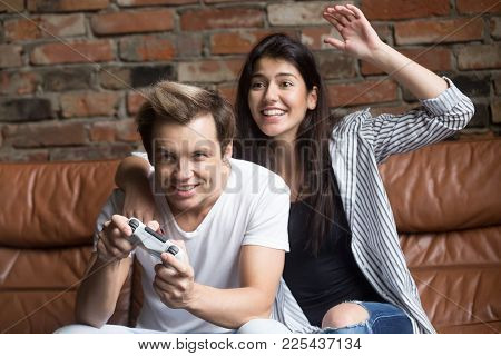 Millennial Couple Playing Video Games, Young Gamer Holding Joystick Controller While Excited Emotion