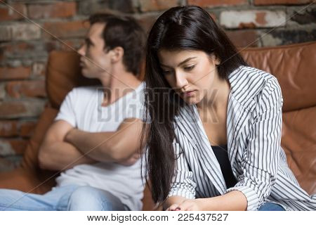Sad Pensive Young Girl Thinking Of Relationships Problems Sitting On Sofa With Offended Boyfriend, C