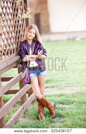 Smiling Blonde Teen Girl 15-16 Year Old Posing Outdoors. Looking At Camera. Spring Season.