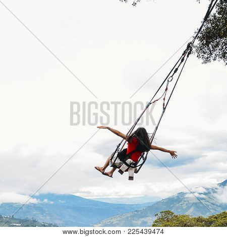 Banos, Ecuador - December 24th, 2017: Young Girl With Arms Outstretched Rides A Swing Overlooking Th