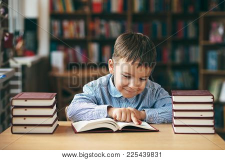 Preschool European Boy Is Staying At The Table In The Library With Stacks Of Books Beside. Close-up