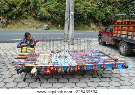 Banos, Ecuador - December 24th, 2017: Local Indigenous Ecuadorian Man Plays The Banjo While Selling