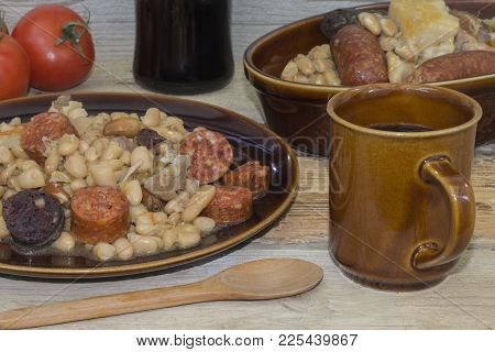 Stew Of Sausages And Beans On A Plate, On A Rustic Wooden Table