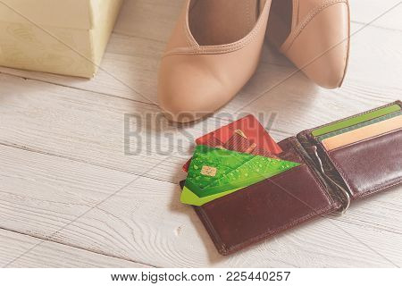Box, Open Wallet, Credit Cards And Womans Shoes Lying On The White Wooden Background.