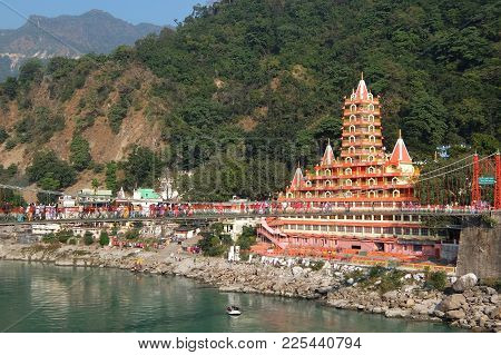 Rishikesh, India - November, 4th, 2017. View Of Ganga River Embankment, Lakshman Jhula Bridge And Te