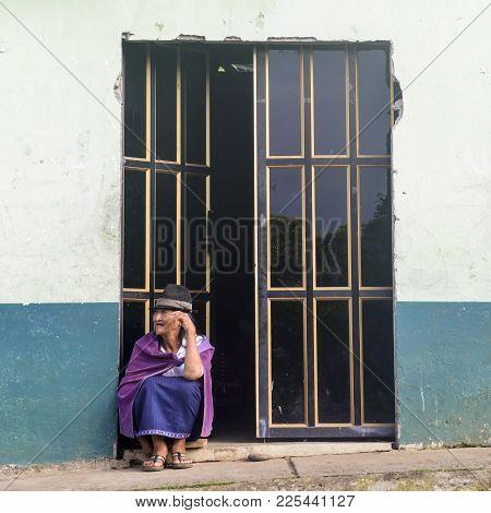 Chimborazo, Ecuador, December 31, 2017: Traditionally Dressed Older Ecuadorian Woman Sitting At Door