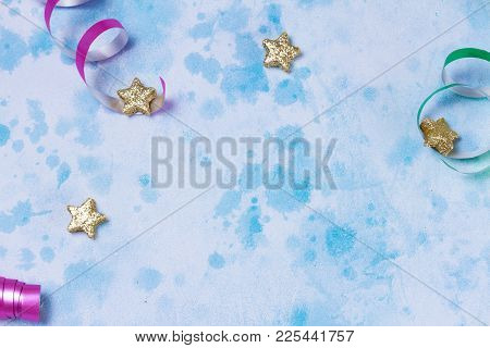 Bright Colorful Carnival Or Party Frame Of Streamers And Confetti On Blue Table Background. Flat Lay