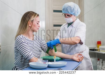 Preparation For Blood Test With Beautiful Young Blond Woman By Female Doctor In White Coat Medical U