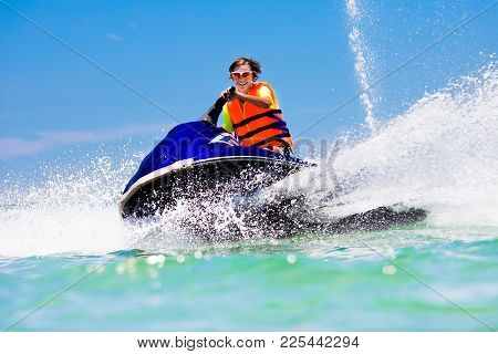 Teenager On Jet Ski. Teen Age Boy Water Skiing.